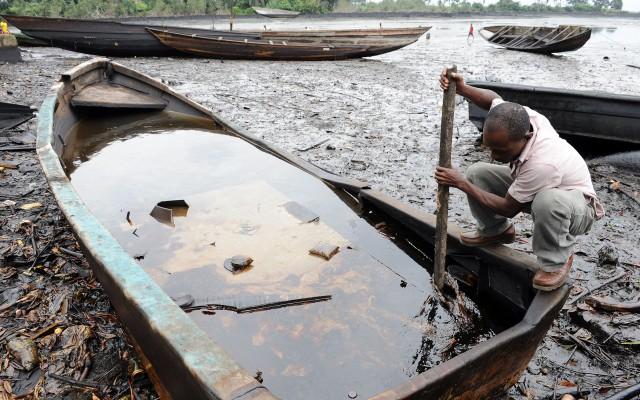 An indigene of Bodo Ogoniland tries to separate the crude oil from water in a boat with a stick at the Bodo waterways polluted by oil spills attributed to Shell equipment failure. Credit Pius Utomi Ekpei